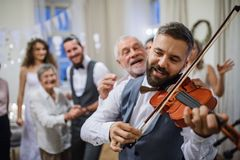A mature man playing a violin on a wedding reception, bride and groom dancing. A mature men playing a violin on a wedding reception, bride, groom and other royalty free stock images