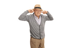 Mature man plugging his ears with his fingers. Isolated on white background Royalty Free Stock Photography