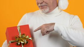 Mature man pointing at red present box, christmas celebration, holiday surprise. Stock footage stock video footage