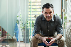 Mature man. Portrait of mature handsome man sitting on chair and looking at camera stock images