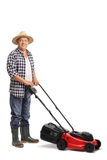 Mature man posing with a red lawn mower Stock Photo
