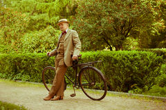 Mature man posing with retro bicycle in the park Stock Images