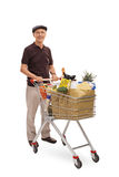 Mature man posing with a shopping cart Royalty Free Stock Images