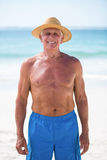 Mature man posing with straw hat Stock Images