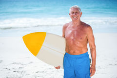 Mature man posing with a surfboard. At the beach Stock Photos