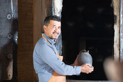 Mature man potter holding black glazed ceramic vessel next to ki Stock Photo
