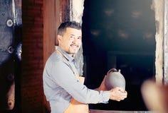 Mature man potter holding black glazed ceramic vessel next to ki. Happy american mature man potter holding black glazed ceramic vessel next to kiln royalty free stock photography