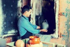 Mature man potter holding black glazed ceramic vessel next to ki Stock Image