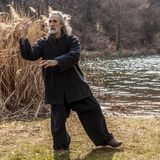 Mature man practicing Tai Chi discipline outdoors. In a lake park on a winter day stock photo