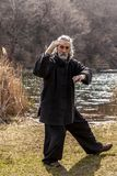 Mature man practicing Tai Chi discipline outdoors. In a lake park on a winter day stock images