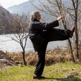 Mature man practicing Tai Chi discipline outdoors. In a lake park on a winter day royalty free stock photos