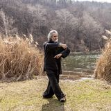 Mature man practicing Tai Chi discipline outdoors. In a lake park on a winter day stock photography
