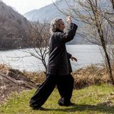 Mature man practicing Tai Chi discipline outdoors. In a lake park on a winter day royalty free stock photography