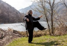 Mature man practicing Tai Chi discipline outdoors. In a lake park on a winter day royalty free stock photo