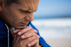 Mature man praying with hands clasped stock photo