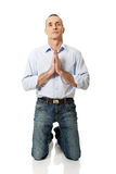 Mature man praying to God on knees Stock Images