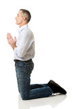 Mature man praying to God on knees Stock Photos