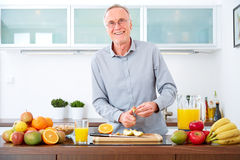 Mature man prepare fruits for breakfast. II Royalty Free Stock Photos
