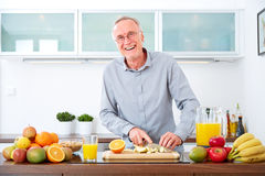 Mature man prepare fruits for breakfast. IV Royalty Free Stock Image