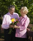 Mature man presenting flowers. royalty free stock photos