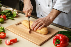 Mature man professional chef cooking meal indoors. Mature male professional chef cooking meal indoors cutting ingredients Stock Image