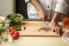Mature man professional chef cooking meal indoors. Mature male professional chef cooking meal indoors cutting ingredients Royalty Free Stock Photography