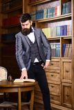 Mature man or professor with long beard and calm face. Historian stands in library and reads old book. Bearded man in elegant suit near bookcase. Historical royalty free stock photo