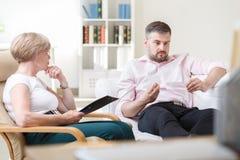 Mature man on psychotherapy session. Mature depressed men on psychotherapy session at home Stock Photo