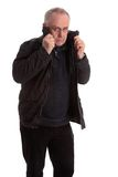 Mature man pulling his jacket up Stock Photography