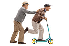 Mature man pushing another man on a scooter Stock Images