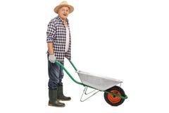 Mature man pushing an empty wheelbarrow stock photos