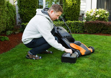 Mature man putting battery into electric Lawn Mower. Photo of mature man putting in battery in electric lawnmower on freshly cut plush green grass with home in royalty free stock photo