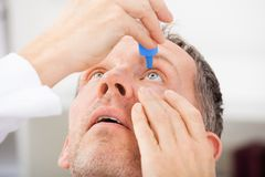 Mature man putting eye drops in eyes Stock Photo