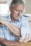 Mature Man Putting Ice Pack On Painful Elbow. Mature Man Puts Ice Pack On Painful Elbow stock photography