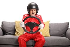 Mature man in a racing suit seated on a sofa holding a steering wheel royalty free stock image