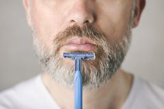 Mature man with razor royalty free stock photography
