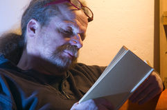 Mature man reading book. Portrait of middle aged or mature man with beard reading book by lamplight stock photography