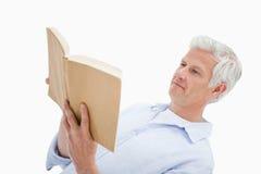 Mature man reading a book Stock Photos