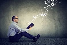 Mature serious man reading a book with alphabet letters coming out of the book royalty free stock images