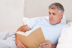Mature man reading book in bed Royalty Free Stock Photo