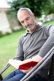 Mature man reading book in garden Stock Image