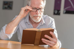 Mature man reading a book Royalty Free Stock Image