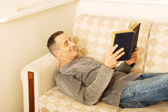 Mature man reading a book at home Royalty Free Stock Image