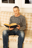 Mature man reading a book at home Stock Photos