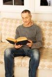Mature man reading a book at home Stock Photos