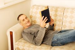 Mature man reading a book at home Royalty Free Stock Photo
