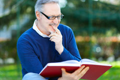 Mature man reading a book outdoor Stock Photo
