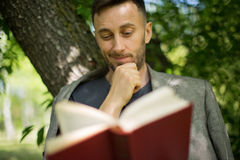 Mature man reading book under the trees in park, psychological c Stock Photography