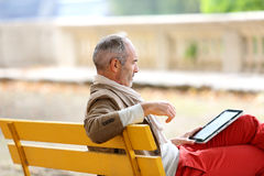 Mature man reading ebook sitting on bench Royalty Free Stock Image