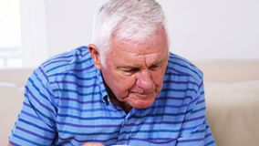 Mature man reading his newspaper and drinking his newspaper. At home stock footage